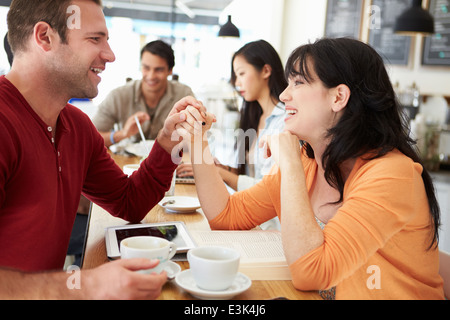 Romantic Couple Meeting In Busy Café - Stock Photo