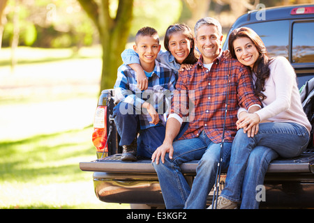 Family Sitting In Pick Up Truck On Camping Holiday - Stock Photo