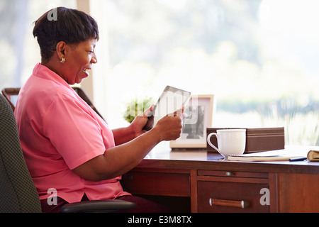 Mature Woman Using Digital Tablet On Desk At Home - Stock Photo