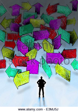 Businessman standing in front of lots of multicolored arrows pointing in different directions - Stock Photo