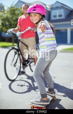 Portrait of smiling girl on skateboard - Stock Photo
