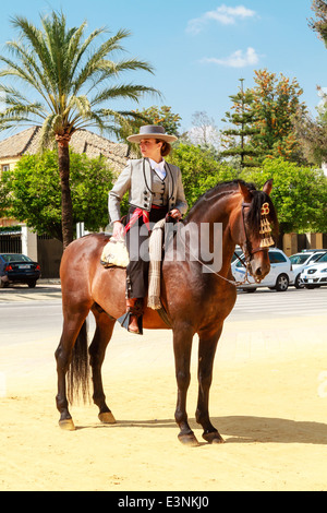 Female rider decked out in flat-topped hat on her horse standing in the street during Feria del Caballon, Spains - Stock Photo