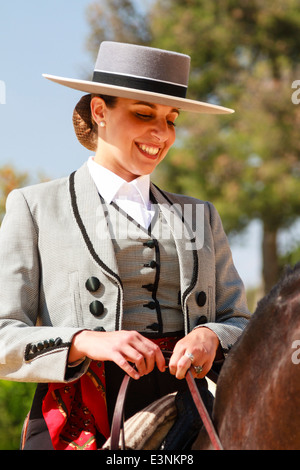 Female rider decked out in traditional flat-topped hat sitting on her horse smiling during Feria del Caballon, Spains - Stock Photo