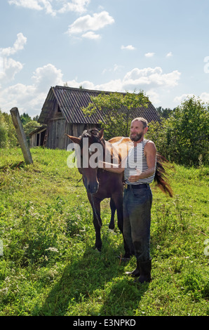 Classical haymaking in the Belarus village. Horse for hay transport on a cart. - Stockfoto