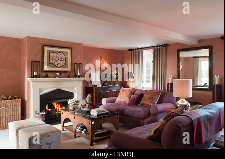 Marble topped coffee table and cow hide seating cubes both design by Beckford in living room with fireplace - Stock Photo