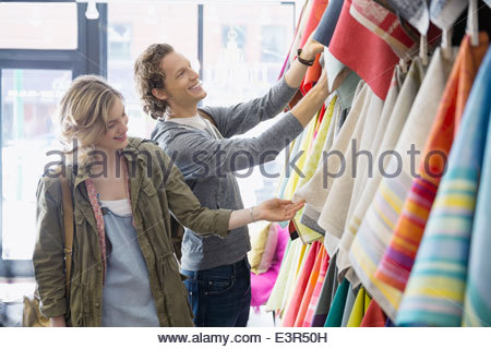 Couple looking at fabric in linens shop - Stock Photo