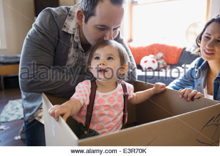 Baby girl playing inside of cardboard box - Stock Photo