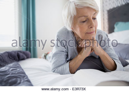 Woman reading book in bed - Stock Photo