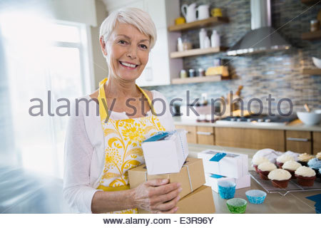 Woman holding boxed cupcakes in kitchen - Stock Photo