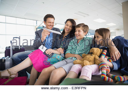Family with toy airplane waiting in airport - Stock Photo
