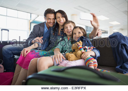 Family taking selfie in airport - Stockfoto