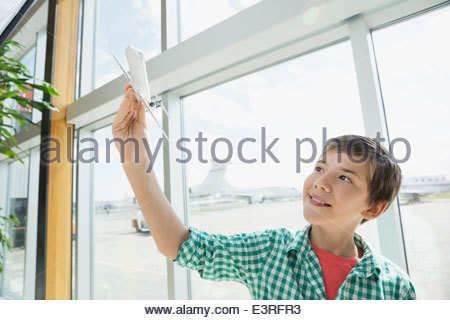 Boy playing with toy airplane in airport - Stockfoto