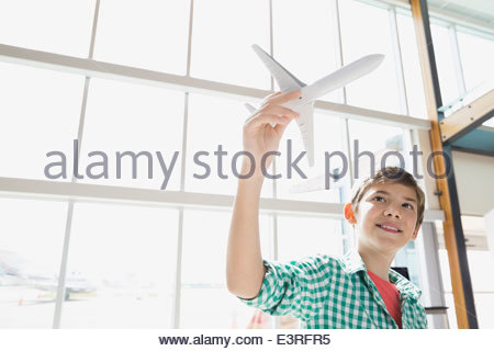 Boy playing with toy airplane in airport - Stock Photo