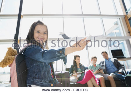Girl playing with toy airplane in airport - Stock Photo