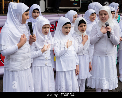 Young girls of Turkish origin who live in Germany sing religious songs, wearing traditional Turkish clothes. - Stock Photo