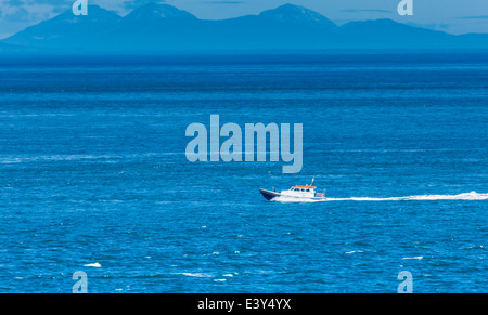 Kintyre Express Ferry in the North Channel seen from Murlough Bay County Antrim with the Paps of Jura in the Background - Stock Photo