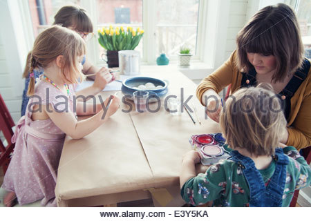 Family painting easter eggs at table - Stock Photo