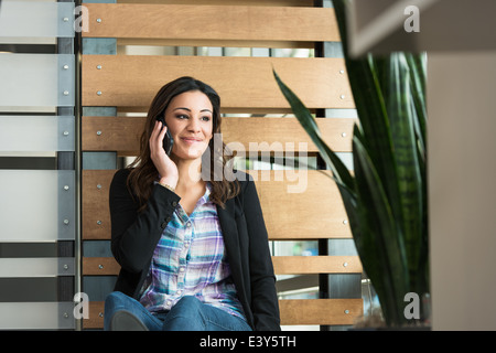 Young female office worker chatting on smartphone in office - Stock Photo