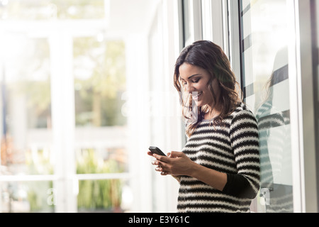 Young businesswoman texting on smartphone in office - Stock Photo