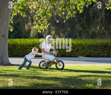 Three year old boy pushing grandmother on cycle in park - Stock Photo