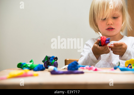 Three year old boy playing with modeling clay - Stock Photo