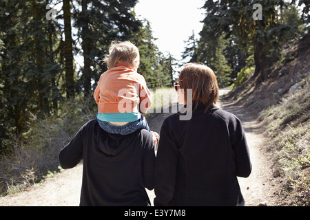 Women walking through forest in Oregon, USA, with toddler sitting on shoulders - Stock Photo