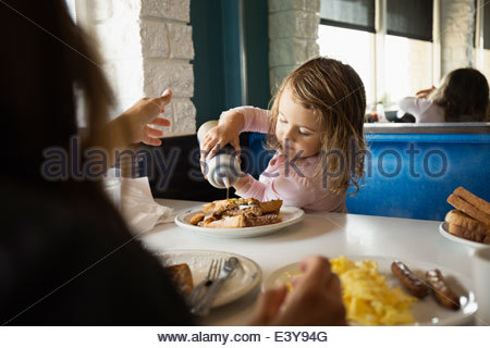 Mother with toddler daughter pouring ketchup in diner - Stock Photo