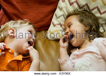 Male and female toddler friends giggling on sofa - Stock Photo