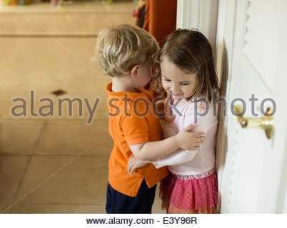Male and female toddler friends with arms around each other - Stock Photo