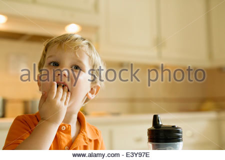 Male toddler eating with hands in kitchen - Stock Photo