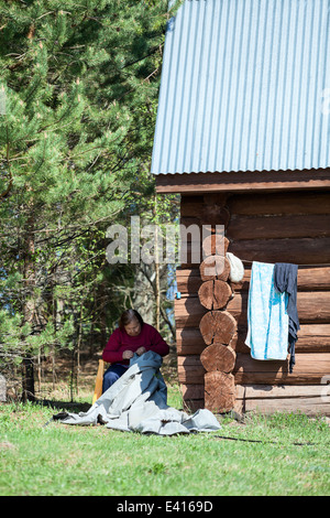 Senior Caucasian needlewoman sitting in shadow and working - Stock Photo