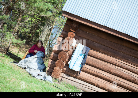 Mature needlewoman sitting in shadow and working near timber house - Stock Photo