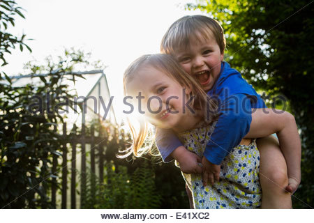 Sister giving brother a piggy back - Stock Photo