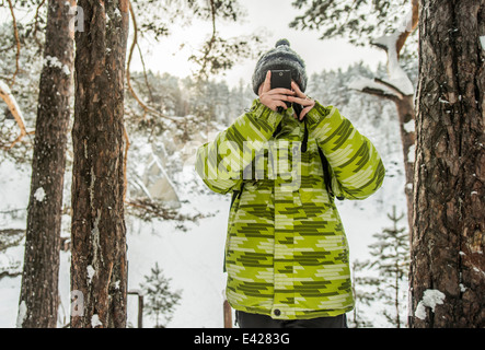 Man taking photograph in snow covered forest, Russia - Stock Photo