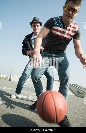 Young men playing basketball in skatepark - Stock Photo