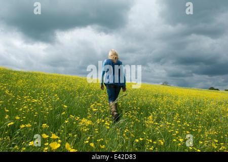 Woman walking in field of buttercups - Stock Photo