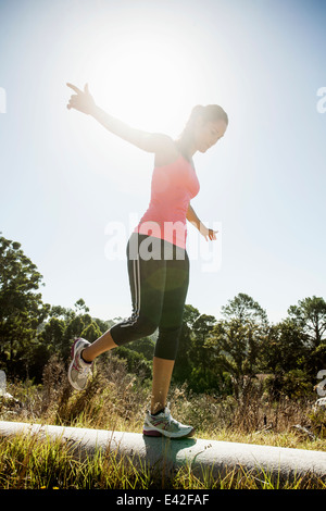 Female jogger balancing on pipe - Stock Photo
