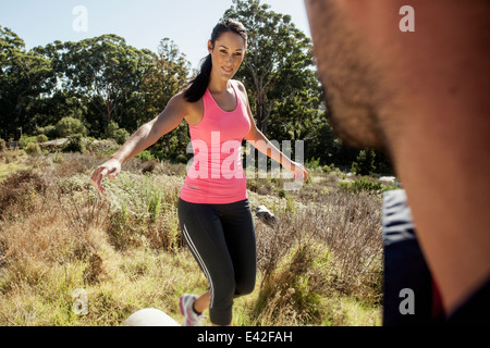 Man looking at female jogger balancing - Stock Photo