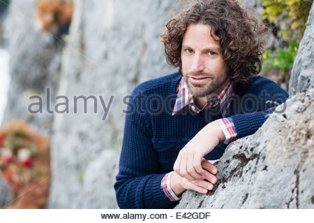 Portrait of mid adult man leaning against rock - Stock Photo