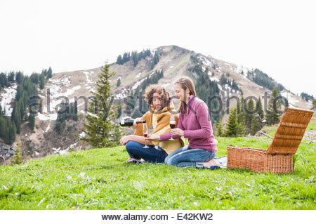 Romantic mid adult couple having champagne picnic, Wallberg, Tegernsee, Bavaria, Germany - Stock Photo