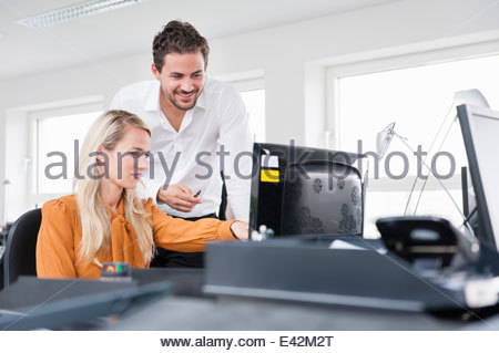 Colleagues using computer in office - Stock Photo