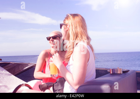 Two adult female friends laughing on board yacht - Stockfoto