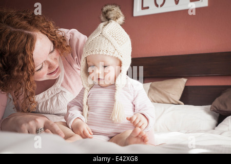 Portrait of mid adult mother and baby girl in knitted hat - Stock Photo