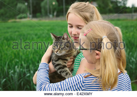 Two sisters in field with domestic cat - Stock Photo