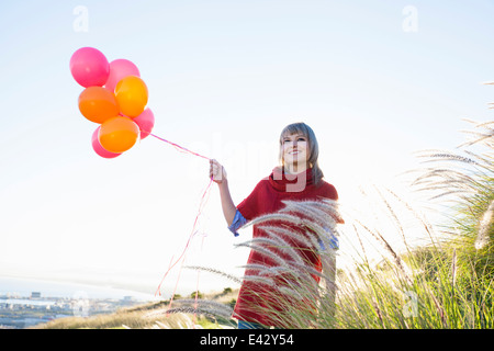 Young woman on grassy hill holding bunch of balloons - Stock Photo