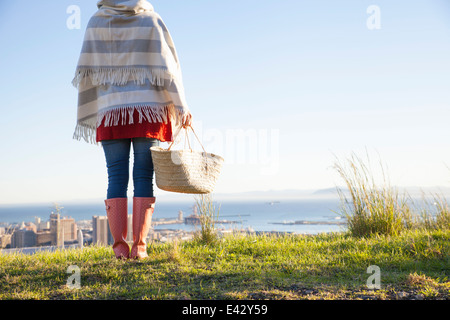 Rear view of young woman on hill with a sea view - Stock Photo