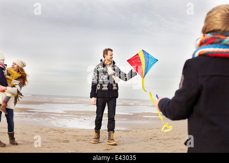 Mid adult parents with son and daughter playing with kite on beach, Bloemendaal aan Zee, Netherlands - Stock Photo