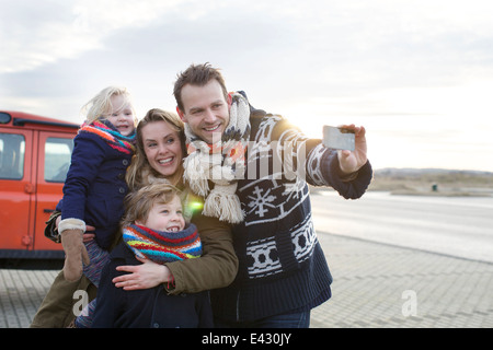 Mid adult man taking a family selfie in coastal parking lot - Stockfoto