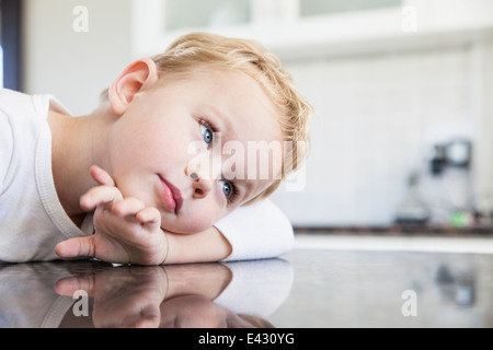 Portrait of three year old boy leaning on kitchen bench - Stock Photo