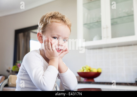 Portrait of cheeky four year old boy in kitchen - Stock Photo